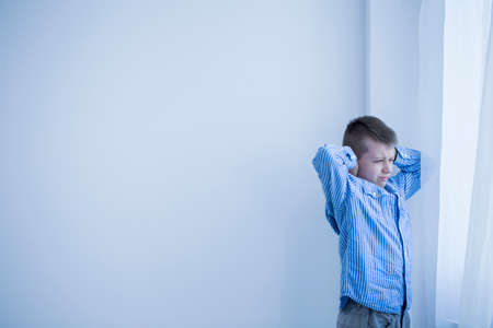 Foto de Young autistic boy in a white, empty room standing next to a window covering his ears - Imagen libre de derechos