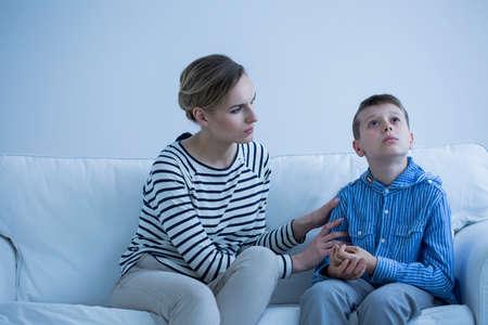 Foto de Autistic boy sitting on a sofa with his carer trying to calm him down - Imagen libre de derechos