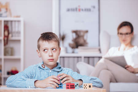 Foto de Autistic boy playing with colorful dice being watched by a psychotherapist sitting in the background - Imagen libre de derechos