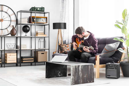 Photo for Musician sitting on a black couch and playing the guitar in modern living room interior. - Royalty Free Image