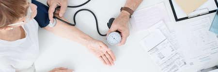 Photo pour Doctor measuring patient's blood pressure with a specialist equipment - image libre de droit