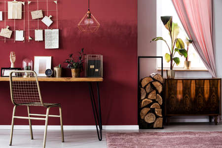 Photo pour Cupboard and logs of wood next to a metal chair at desk with clock in workspace interior - image libre de droit