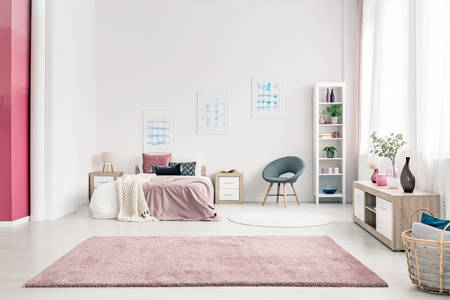 Photo for Pink carpet in spacious bedroom interior with grey chair next to bed against the wall with posters - Royalty Free Image