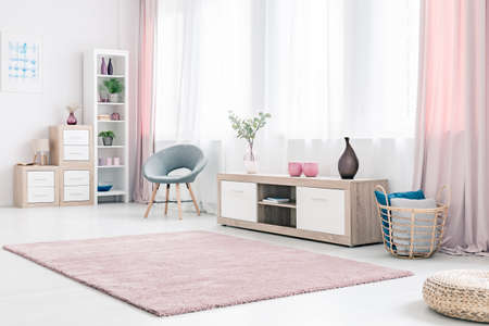 Photo pour Grey armchair next to a wooden cupboard with dark vase in spacious, pink living room interior - image libre de droit