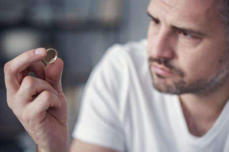 Photo pour Disappointed man holding his wedding ring after divorce - image libre de droit