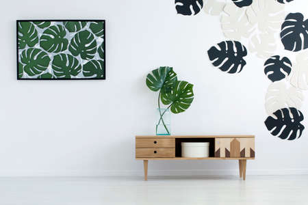 Photo pour Wooden cupboard against the wall with monstera leaves poster and stickers in living room interior - image libre de droit