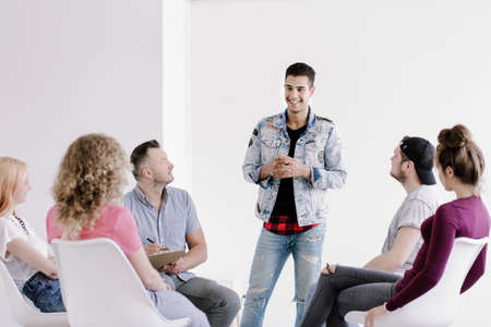 Photo for Smiling young man in jeans and denim jacket standing and talking about his progress during group therapy for rebellious youth - Royalty Free Image