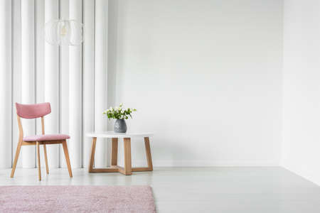 Foto de Pink, wooden chair and coffee table next to an empty wall in a living room interior - Imagen libre de derechos