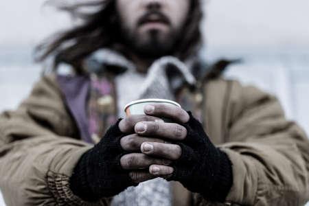 Foto de Photo of a homeless man with close-up of dirty hands holding a paper cup - Imagen libre de derechos