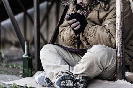 Foto de Close-up photo of homeless man sitting on the ground with an empty bottle next to him - Imagen libre de derechos