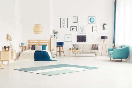 Foto de Blue carpet and armchair in bright open space interior with bed near sofa next to wooden lamp - Imagen libre de derechos