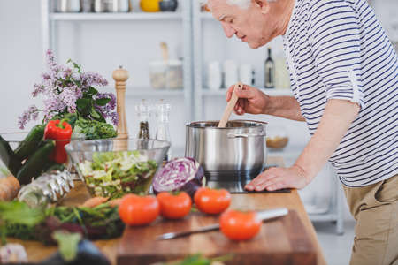 Foto de Elderly man smelling healthy tomato soup in the kitchen with vegetables - Imagen libre de derechos