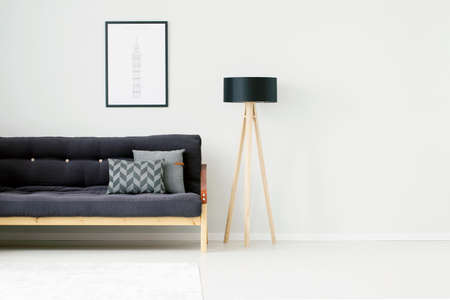 Foto de Wooden lamp against white, empty wall in living room interior with gray pillows on black couch - Imagen libre de derechos