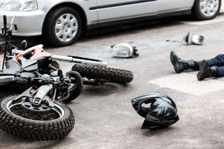 Foto de Legs of a person lying on the road after a motorcycle and car accident - Imagen libre de derechos