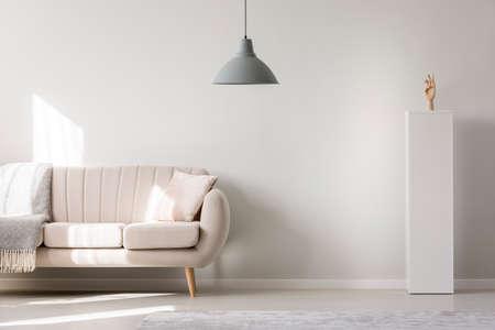Foto de Sofa and grey lamp hanging in living room interior with empty white wall - Imagen libre de derechos
