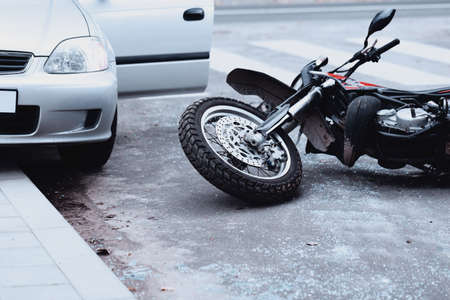 Foto de Motorcycle lying on the road and car standing with open door after a collision - Imagen libre de derechos