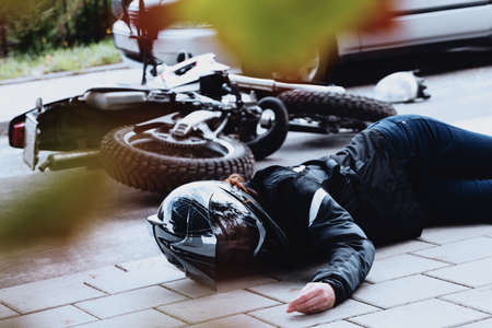 Foto de Female motorcyclist lying unconscious on the pavement after having an accident on the road - Imagen libre de derechos