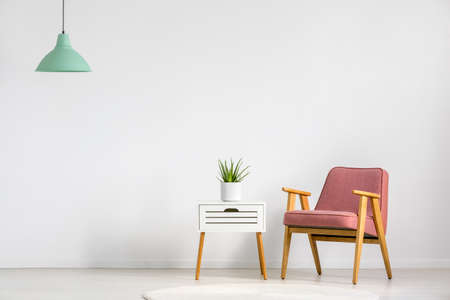 Photo for Pink armchair and wooden table on empty wall in simple living room interior - Royalty Free Image