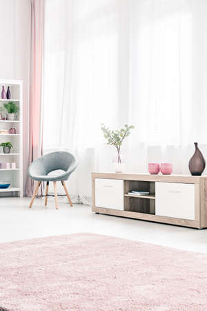 Photo for Grey armchair next to a wooden cupboard in bright, pastel living room interior with pink carpet - Royalty Free Image