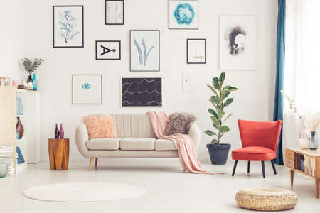 Photo for Pouf, round rug and red armchair in colorful living room interior with beige sofa and posters - Royalty Free Image