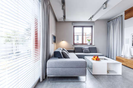 Photo pour Grey corner couch near white table with oranges in modern living room interior - image libre de droit