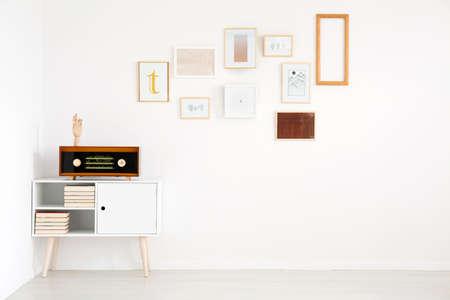 Foto de Minimalism in living room interior with pictures gallery on white, empty wall and vintage radio on cupboard - Imagen libre de derechos