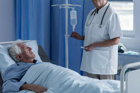 Photo for Doctor in white uniform setting his elder patient's drip - Royalty Free Image