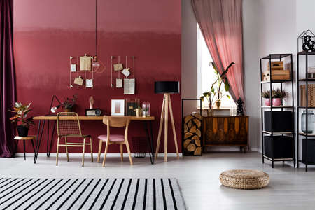 Foto de Striped carpet and pouf in spacious, red workspace interior with window and chairs at table - Imagen libre de derechos