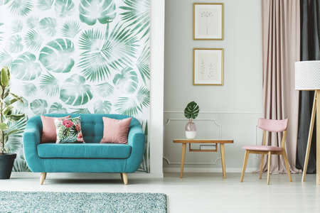 Photo pour Cozy turquoise couch, wooden table and chair in a white and green living room interior with plants and leaf patterns - image libre de droit