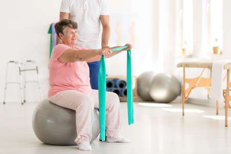 Photo pour Elderly woman sitting on a grey ball and stretching an elastic tape - image libre de droit
