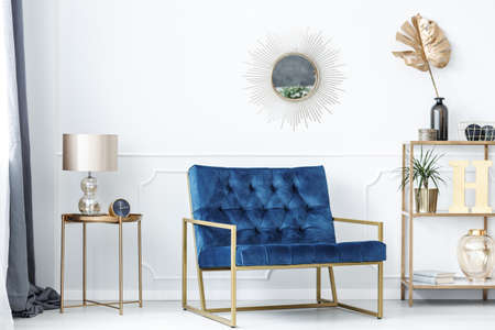 Photo for Blue bench between gold table with lamp and shelves with leaves in glamor living room interior - Royalty Free Image