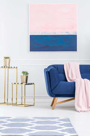 Photo for Plant on gold table in pink and blue apartment interior with couch and painting on white wall - Royalty Free Image