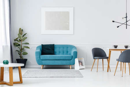 Foto de Turquoise couch against white wall with painting in flat interior with ficus and chairs at table - Imagen libre de derechos