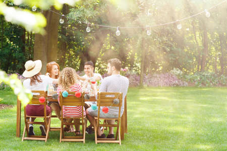 Photo for Group of smiling friends eating lunch at  a garden party - Royalty Free Image