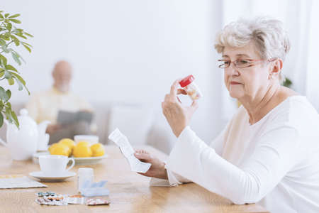 Foto de Sad senior woman sitting at the table with tablets and prescription - Imagen libre de derechos