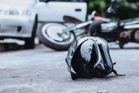 Foto de Close-up of a black biker helmet on the street with overturned motorbike in the background. Road collision concept - Imagen libre de derechos