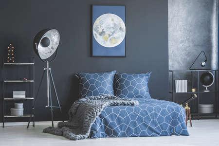 Foto de Industrial lamp next to bed with navy blue bedding against dark wall with moon poster in bedroom interior - Imagen libre de derechos