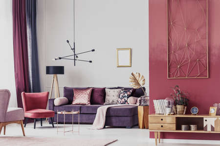 Photo pour Red armchair next to a purple settee in cozy living room interior with wooden cupboard and lamp - image libre de droit