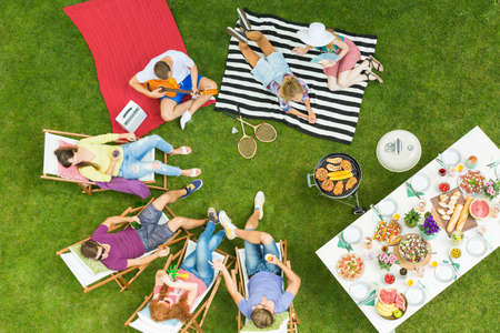 Photo for Top view of group of young friends having summer barbecue party in the backyard with grill and table full of delicious food - Royalty Free Image