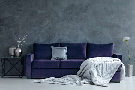 Photo for Grey blanket on violet couch next to table with silver vases in living room interior with concrete wall - Royalty Free Image