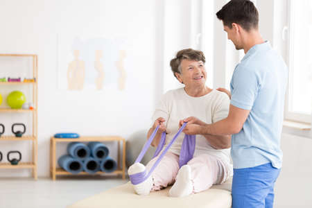 Photo pour Elderly woman exercising her leg with a stretch band with assistance of a young physiotherapist - image libre de droit