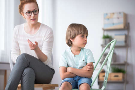 Foto de Psychologist in glasses with angry kid sitting and looking the other way with his arms crossed - Imagen libre de derechos