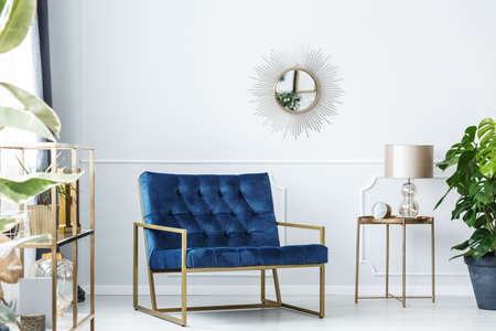 Foto de Navy blue armchair next to gold table with lamp against white wall with mirror in living room interior - Imagen libre de derechos