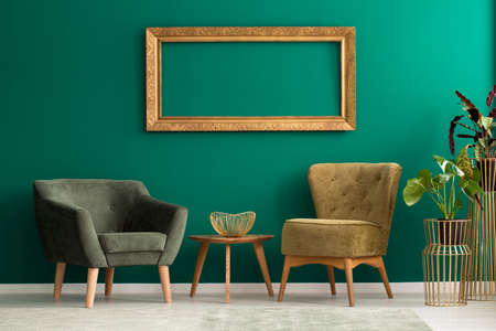 Photo for Empty frame above retro, upholstered chairs in a green living room interior with plants and golden decorations - Royalty Free Image