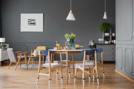 Foto de A wooden table and chairs in grey dining room interior with black walls - Imagen libre de derechos