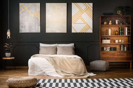 Foto de Elegant, wooden, antique bookcase in a dark, modern bedroom interior with a black wall and beige paintings with golden elements - Imagen libre de derechos