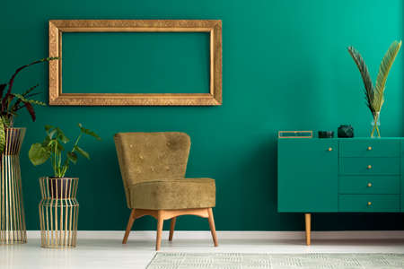 Photo for Palm leaf on a modern, teal sideboard with drawers in a luxurious, green living room interior with golden decorations and an upholstered chair - Royalty Free Image