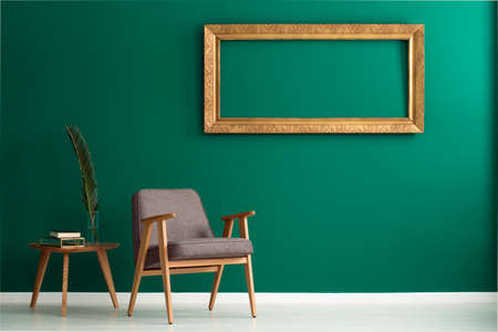 Foto de Empty golden frame on a green wall, palm tree leaf in a vase on a wooden side table and an armchair in a living room interior - Imagen libre de derechos