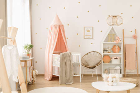 Photo for Sweet, spacious nursery room interior for a baby girl with white furniture, pastel pink decorations and golden polka dot wallpaper - Royalty Free Image