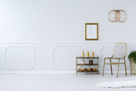 Foto de Gold chair against white wall with molding in living room interior with poster and copy space - Imagen libre de derechos
